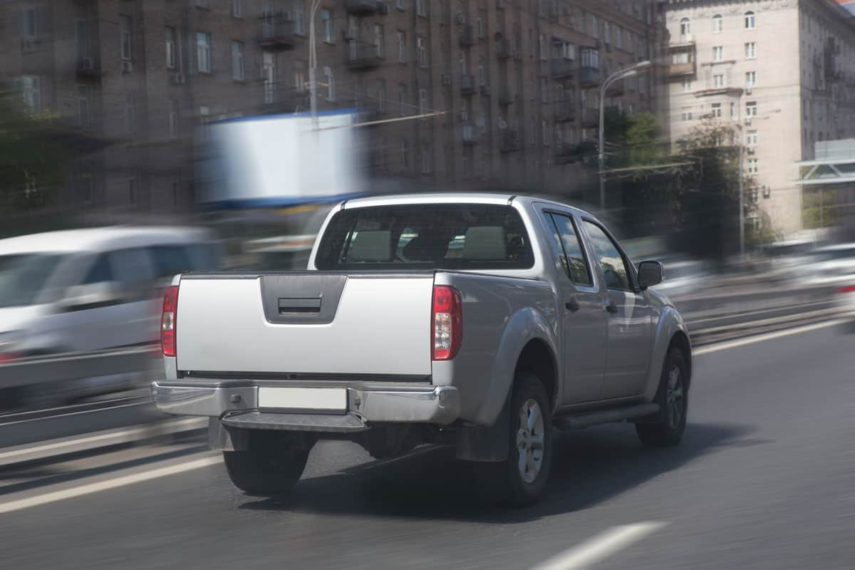 You can drive in 4WD mode on paved roads, A gray Nissan Navara on the road