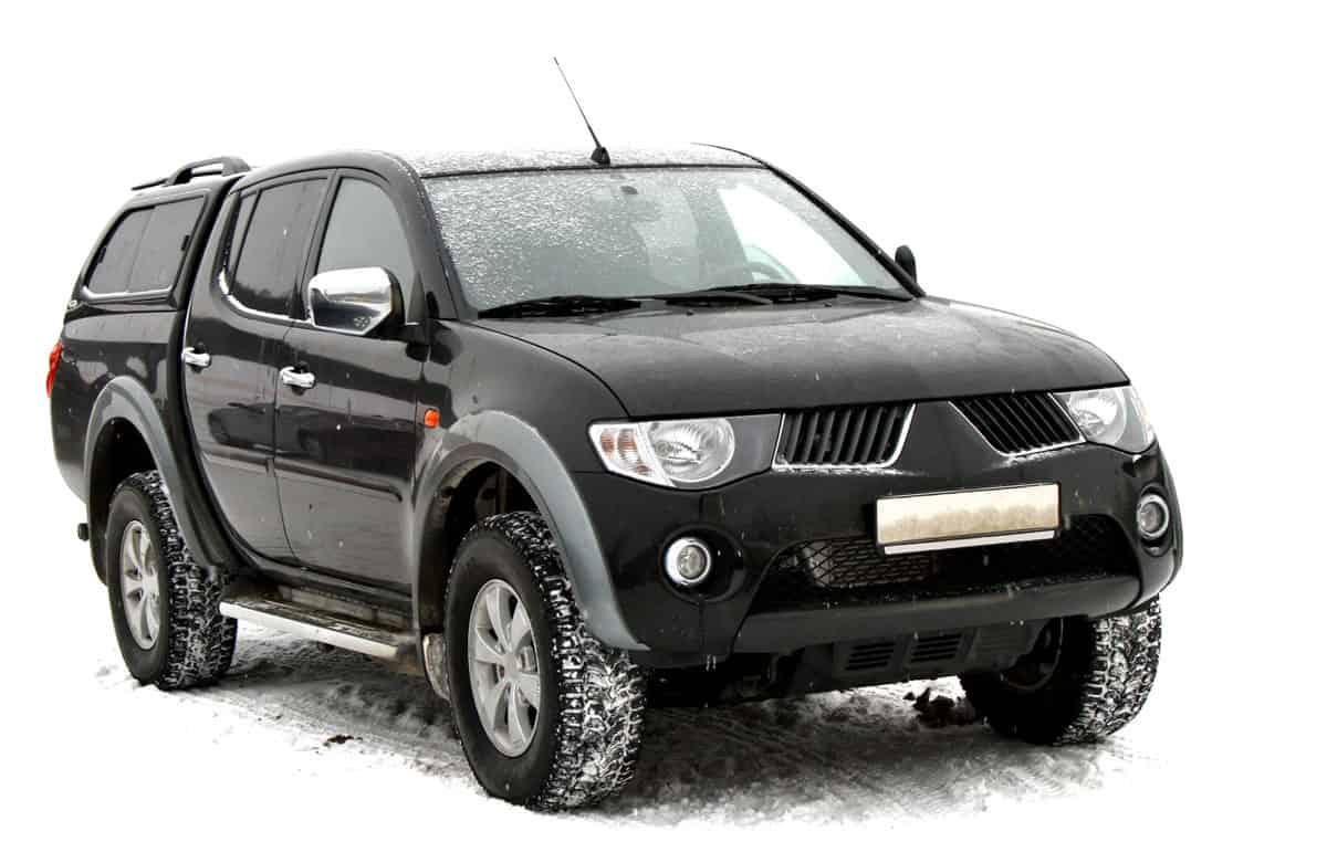 A black Mitsubishi Strada trekking in snowy terrain
