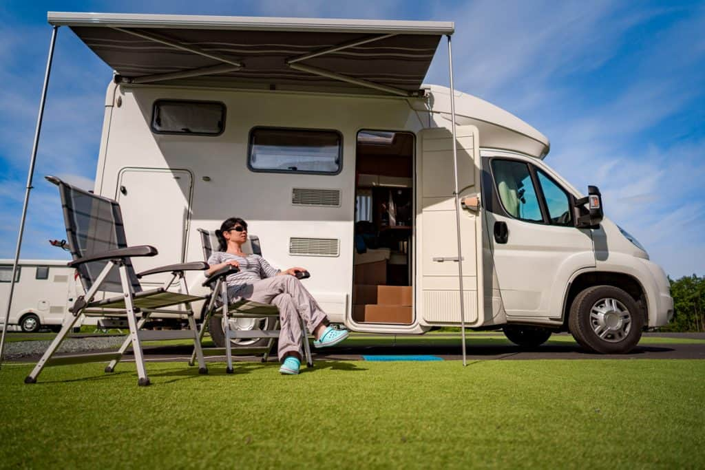 Woman next to a motorhome. Is this the perfect vacation?
