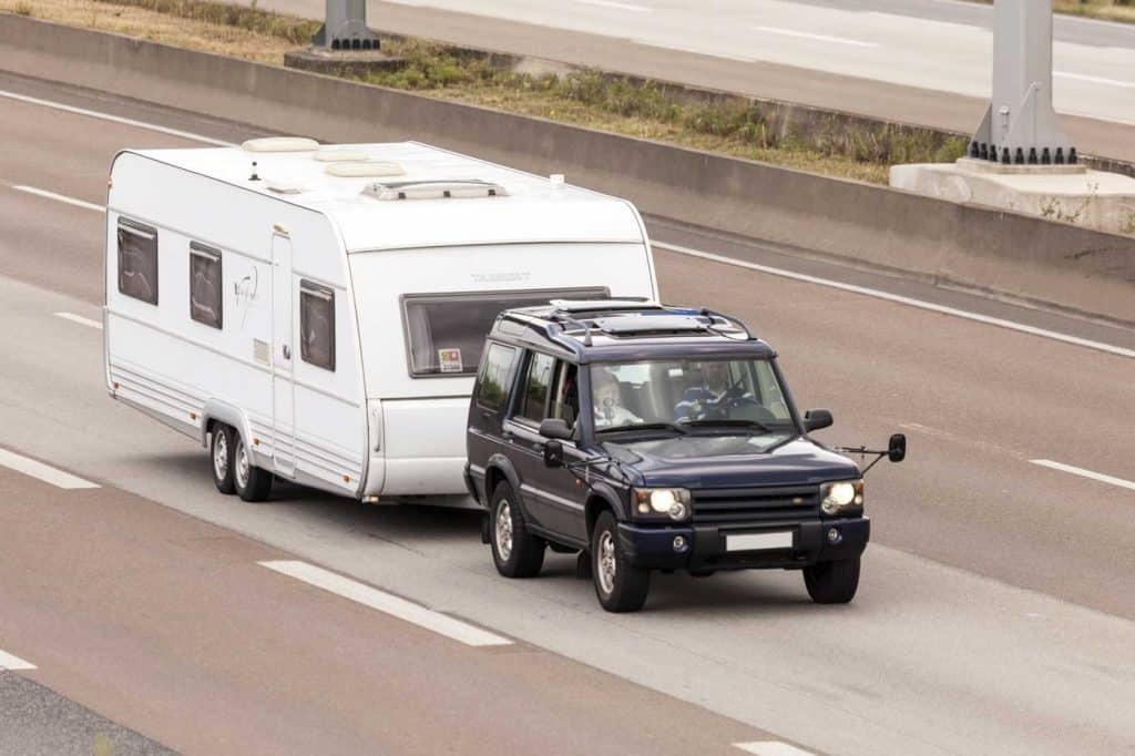 Land Rover towing an RV on the highway