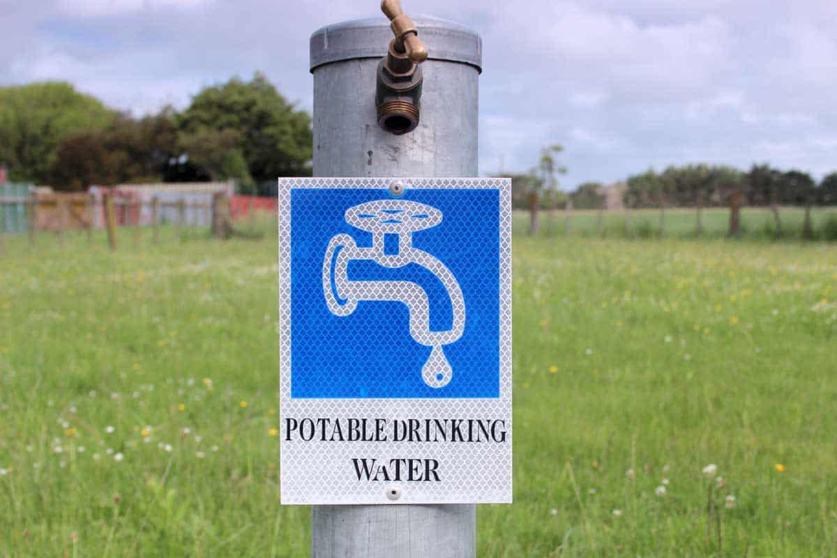 Portable drinking water tap with a sign which a Campervan would use to top up water.