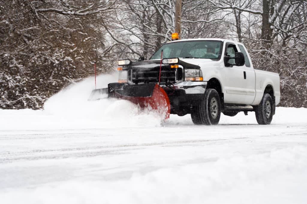 A truck plowing snow using its bulldozer attachment on the front