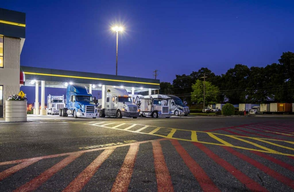 A truck stop where an RV can park overnight, Different make and models big rigs semi trucks with semi trailers standing on the truck stop parking lot under the lighted shelter in night and comply with the movement according to the schedule