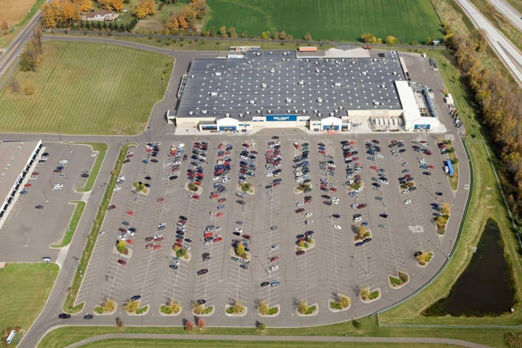 Wal-Mart Supercenter aerial view with free parking for RV, strip mall and a portion of a highway