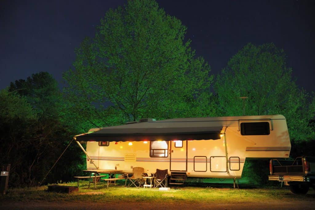A RV parked on a forest with its lights on