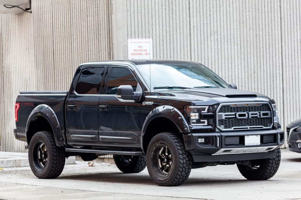 A new Ford F150 Raptor parked on the side of the street