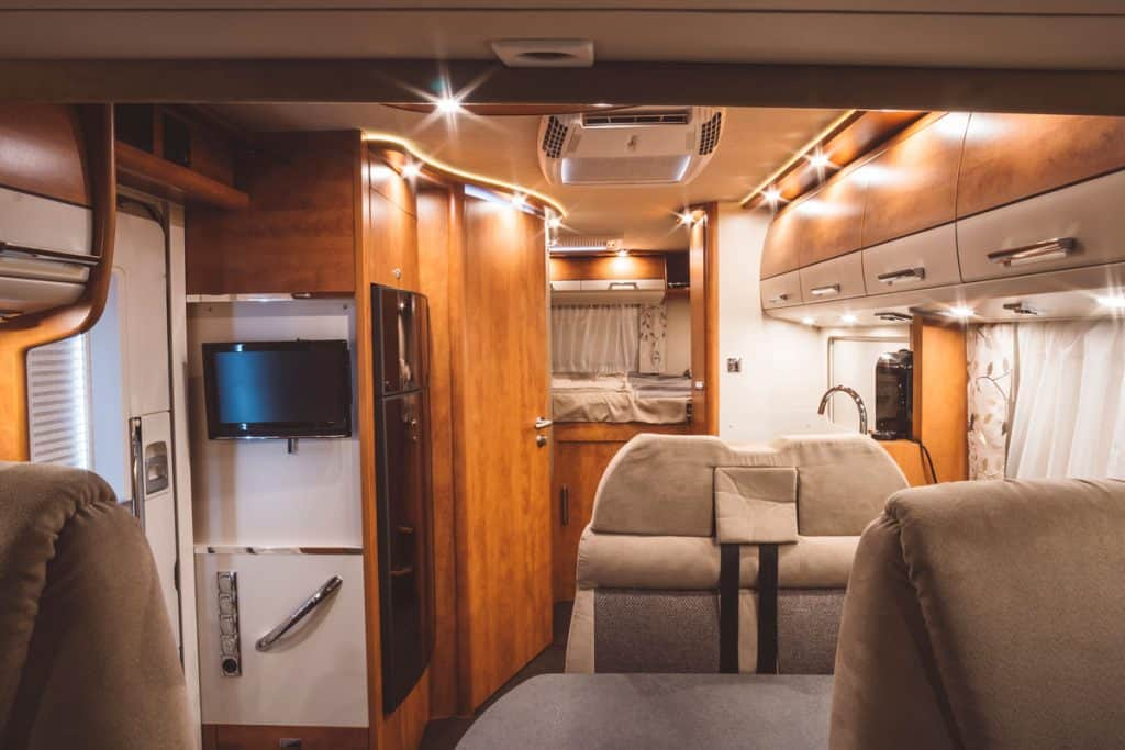 An interior of an RV that has wooden panels and cladding