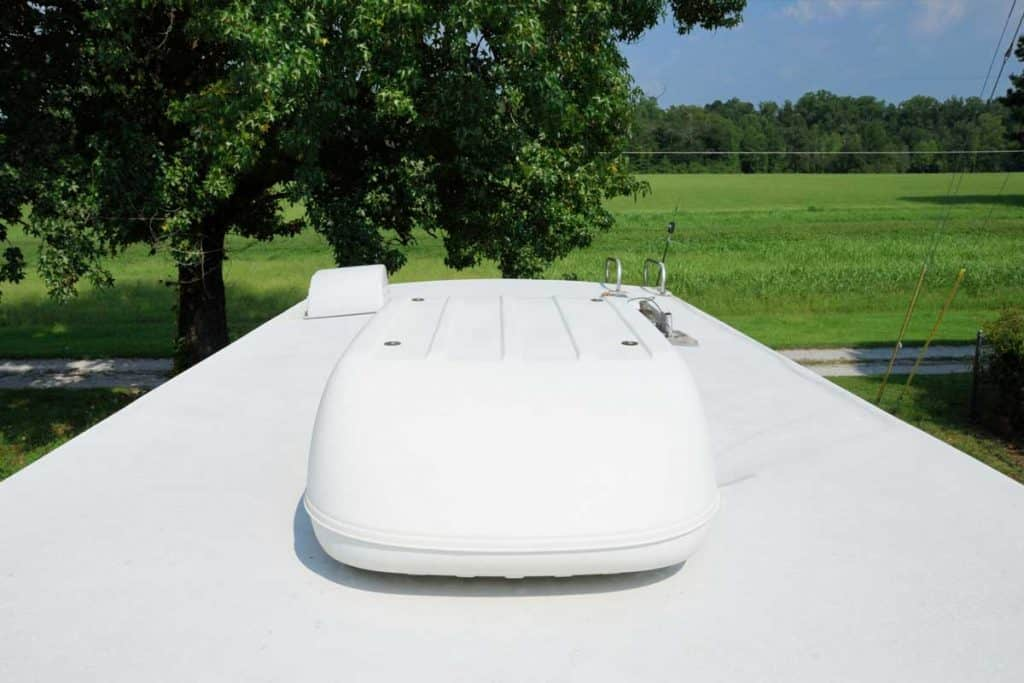 Photograph on roof of recreational vehicle looking into large field. RV roof has large air conditioning unit, ladder, and roof vents.