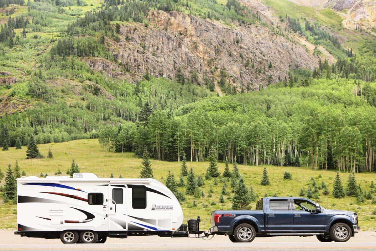A Ford F-150 truck and Lance travel trailer are pulled to the roadside in the San Juan Mountains.