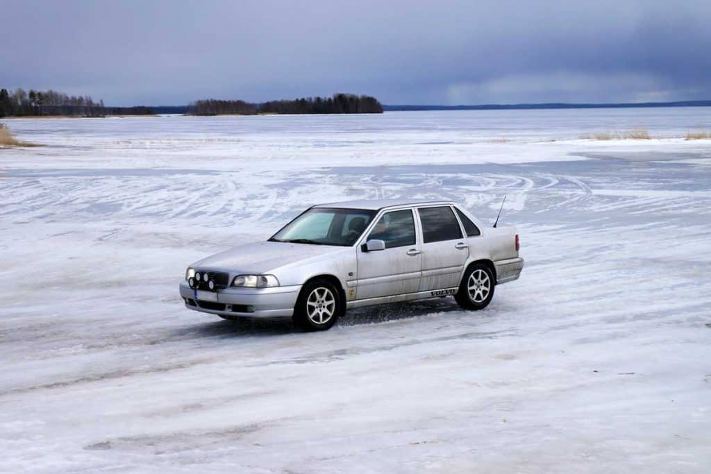 Car driving on an icy road, winter, old car on a frozen road
