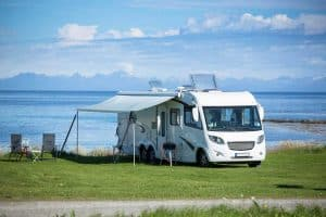 Parked RV near the ocean with an open awning, RV Awning Stuck: What To Do? featured image