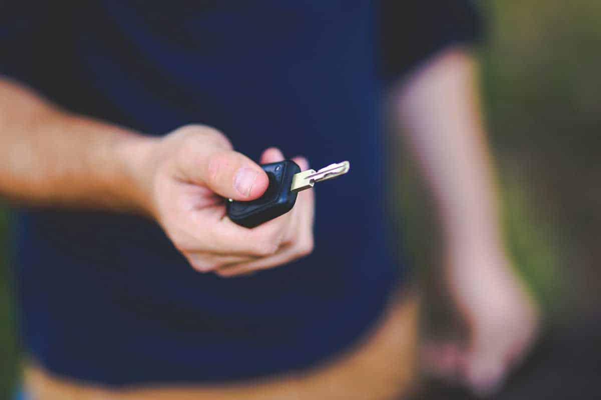 Man pressing lock/unlock button on car key