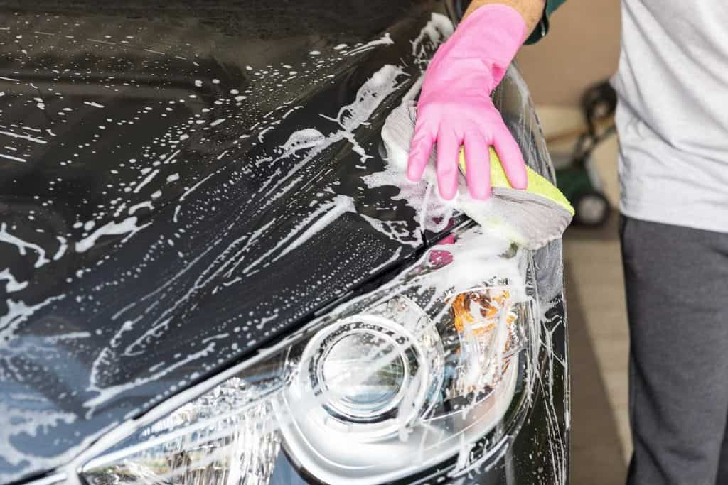 Man washing away bubble on car