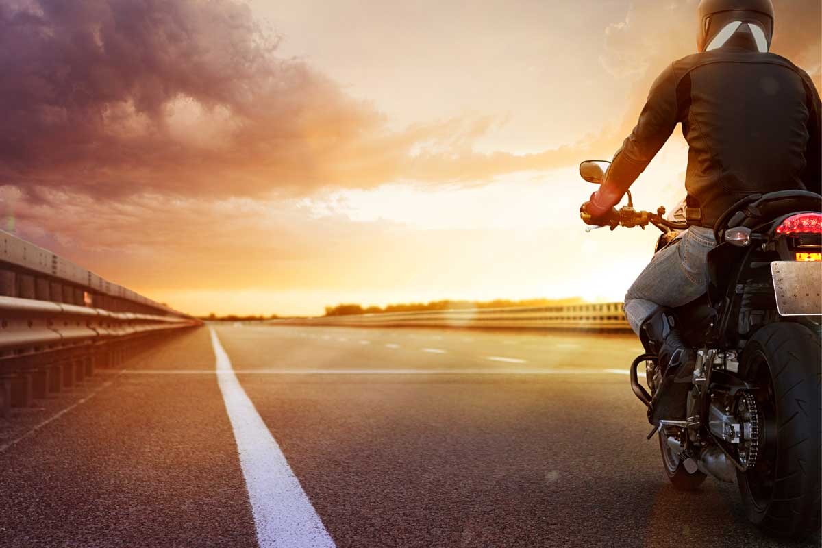 Biker-riding-motorcycle-on-an-empty-road-at-sunset