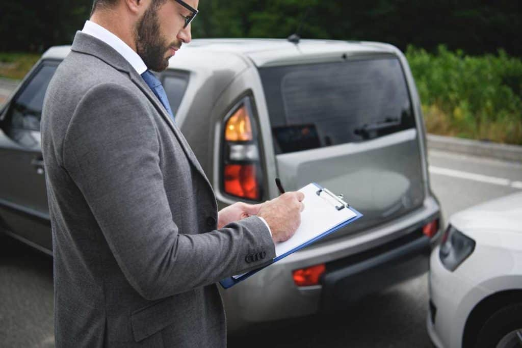 Car insurance agent checking for damages inflicted by car