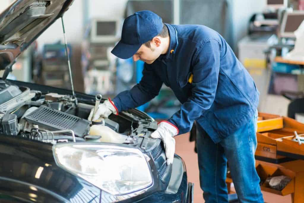 Car mechanic checking engine