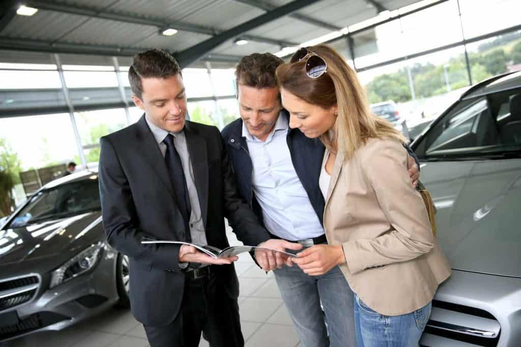 Couples having discussion with dealer holding out a car magazine