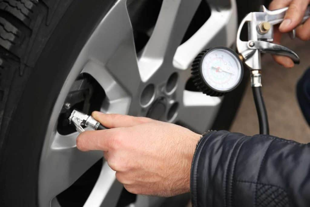 Man checking tire pressure using tire pressure gauge