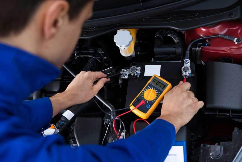 Mechanic checking battery using battery tester equipment
