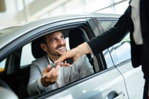 Man accepting keys from seller after buying his new car