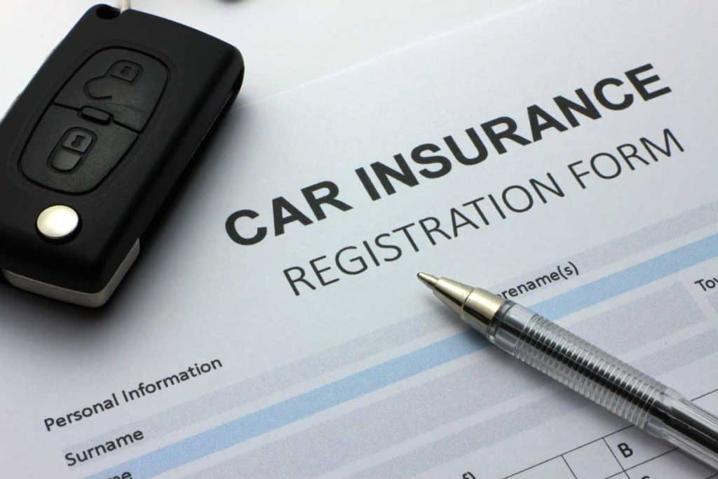 Car insurance registration form with car keys and pen