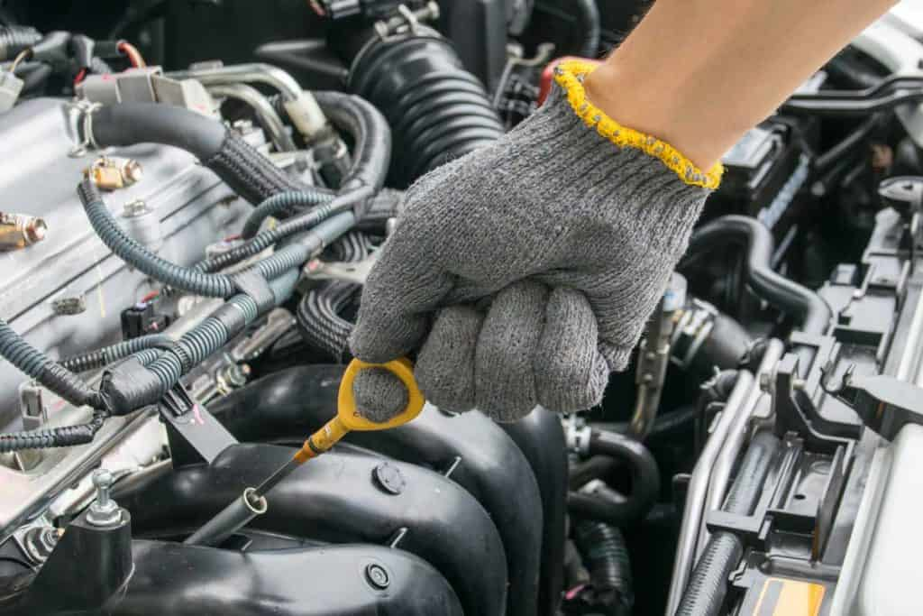 Mechanic checking oil levels of engine