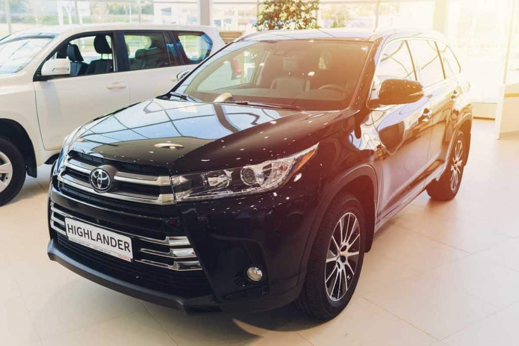 Where-is-the-Toyota-Highlander-Made, Toyota Highlander in a show room beside a Land Cruiser Prado