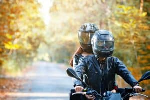 Couple wearing helmets driving down the road on motorcycle, 10 Types of Motorcycle Helmets