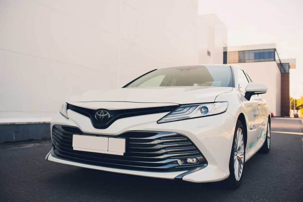 White Toyota Camry parked near building