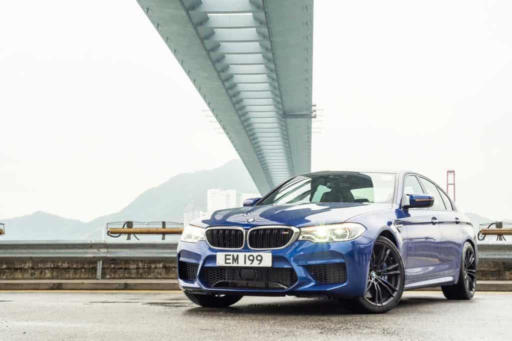 Blue BMW 5 Series parked under bridge at broad daylight