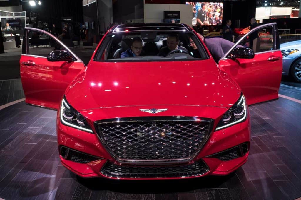 Red Genesis G80 with open doors at car show