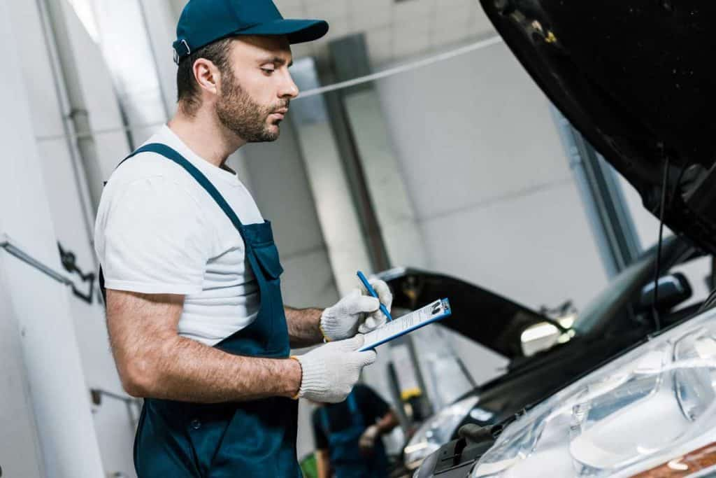 Car mechanic holding his checklist while going through engine inspection