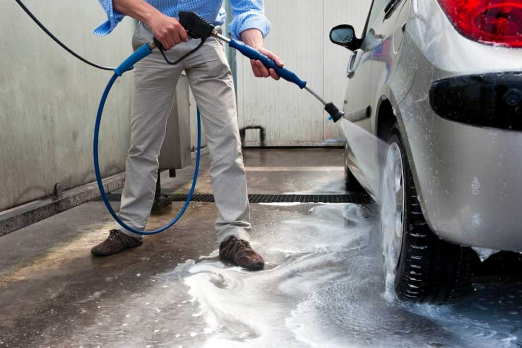 Man using power hose to wash off foam in car