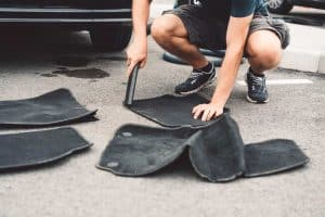 Man using vacuum to clean car floor mats