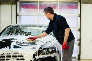 Man washing car hood using sponge, How Often Should You Wash Your Car?