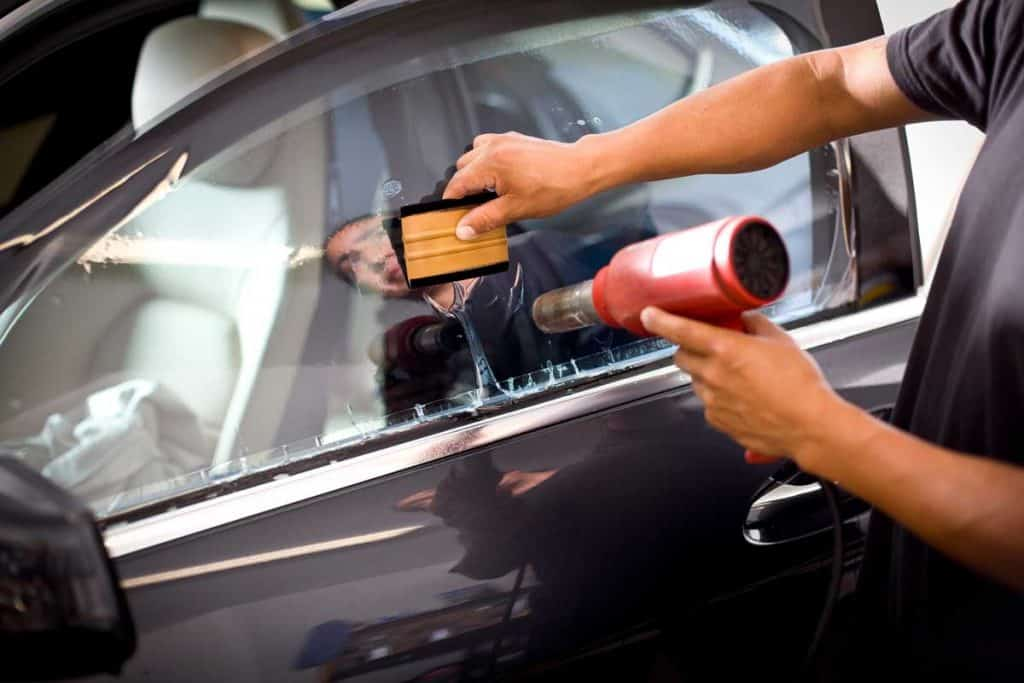 Car specialist applying tint film in cars driver side windshield
