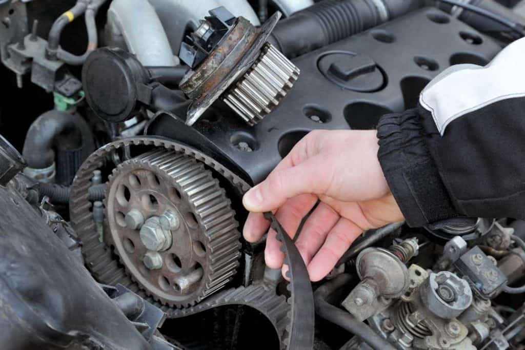 Mechanic changing timing belt of car in engine