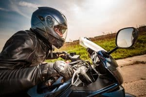 Motorcycle rider with helmet and jacket ducking down and revving up to accelerate, Where To Buy Motorcycle Gear [Top 40 online stores]