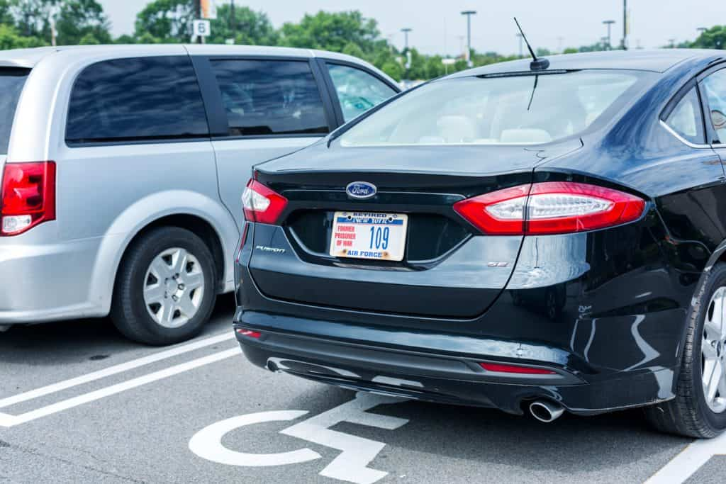 A Ford Fusion with a former prisoner of war license plate on a parking lot in New York