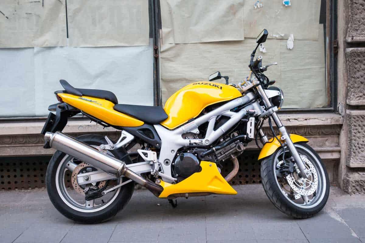 A Suzuki SV650 sports motorcycle parked on a sidewalk.