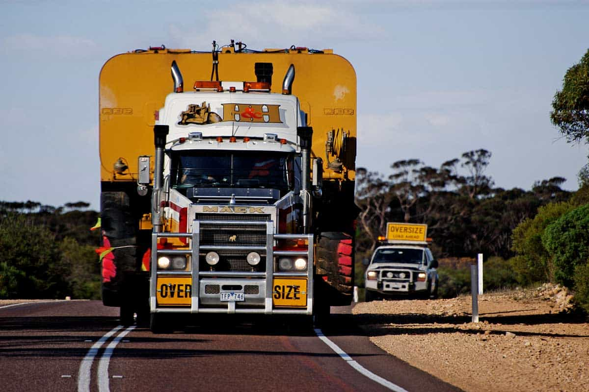 A huge truck with a large width followed by safety of a car indicating to other users of the danger on a road
