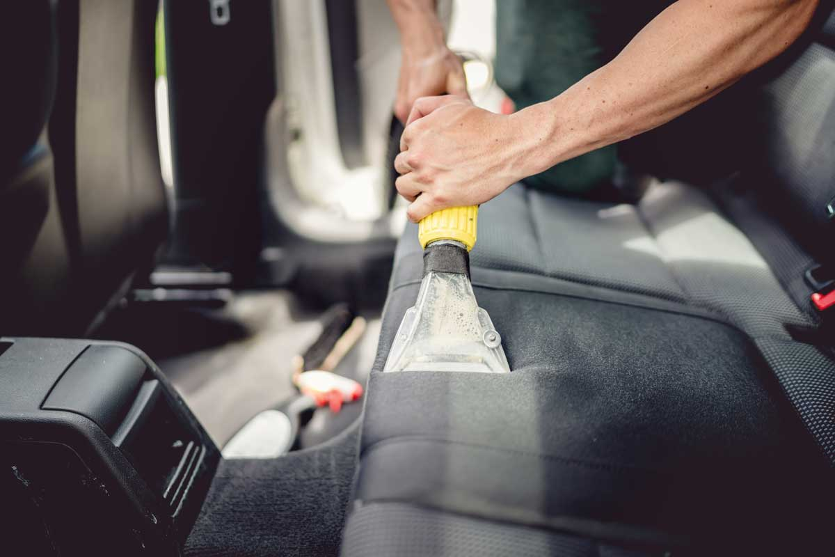 A man cleaning the car rear seat using vacuum