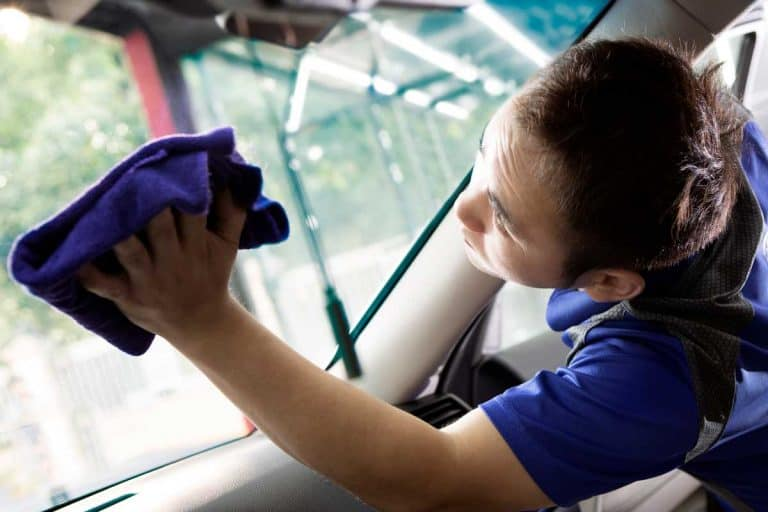 A man cleaning the inside of the windshield using microfiber cloth, How to Clean the Inside of Your Car's Windshield