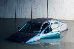 Blue car flooded on a freeway with door left open, Flood Damaged Cars - What Are The Common Problems?