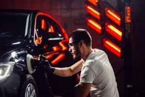 """What Does """"Detailing A Car"""" Mean?, Car detailing - Hands with orbital polisher in auto repair shop. Selective focus."""