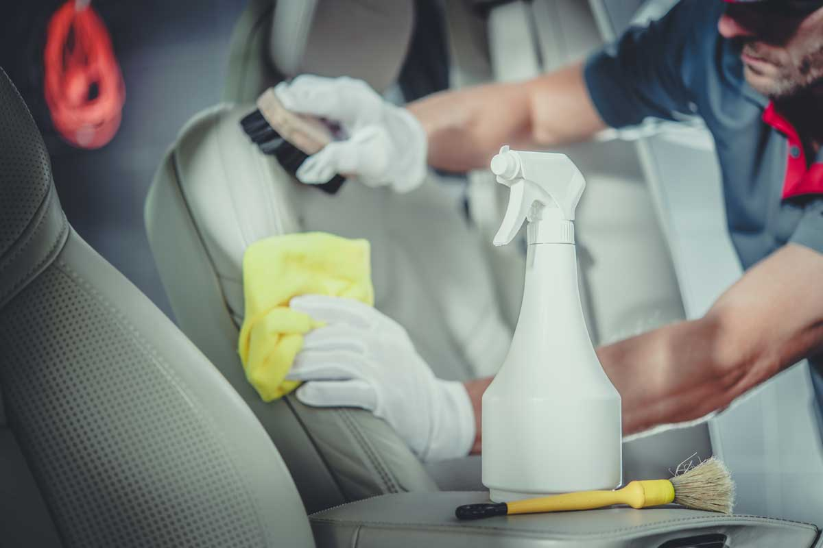 Caucasian Men Cleaning Car Interior. Professional Detailed Vehicle Maintenance.