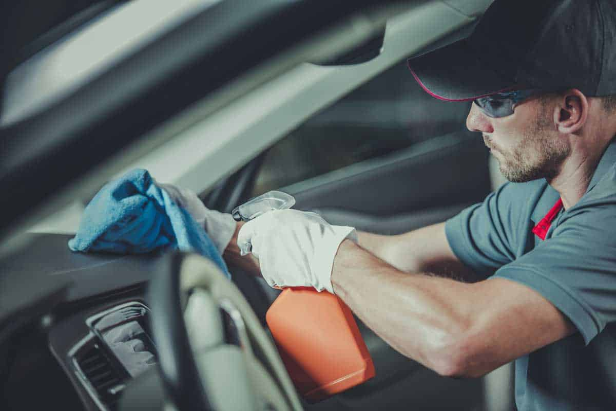 Caucasian Professional Worker Cleaning Modern Car Interior. Vehicle Detailing.