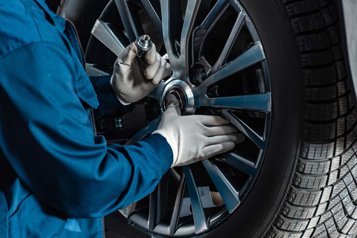 Cropped view of mechanic fixing wheel on car in workshop to stop whistle noise when driving
