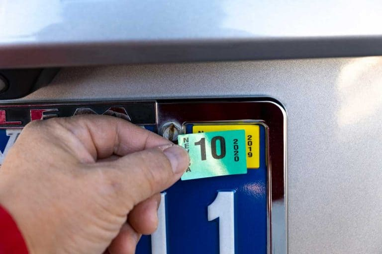 Man placing 2020 sticker into license plate, What Are Car Tags [And What To Do When They Expire]