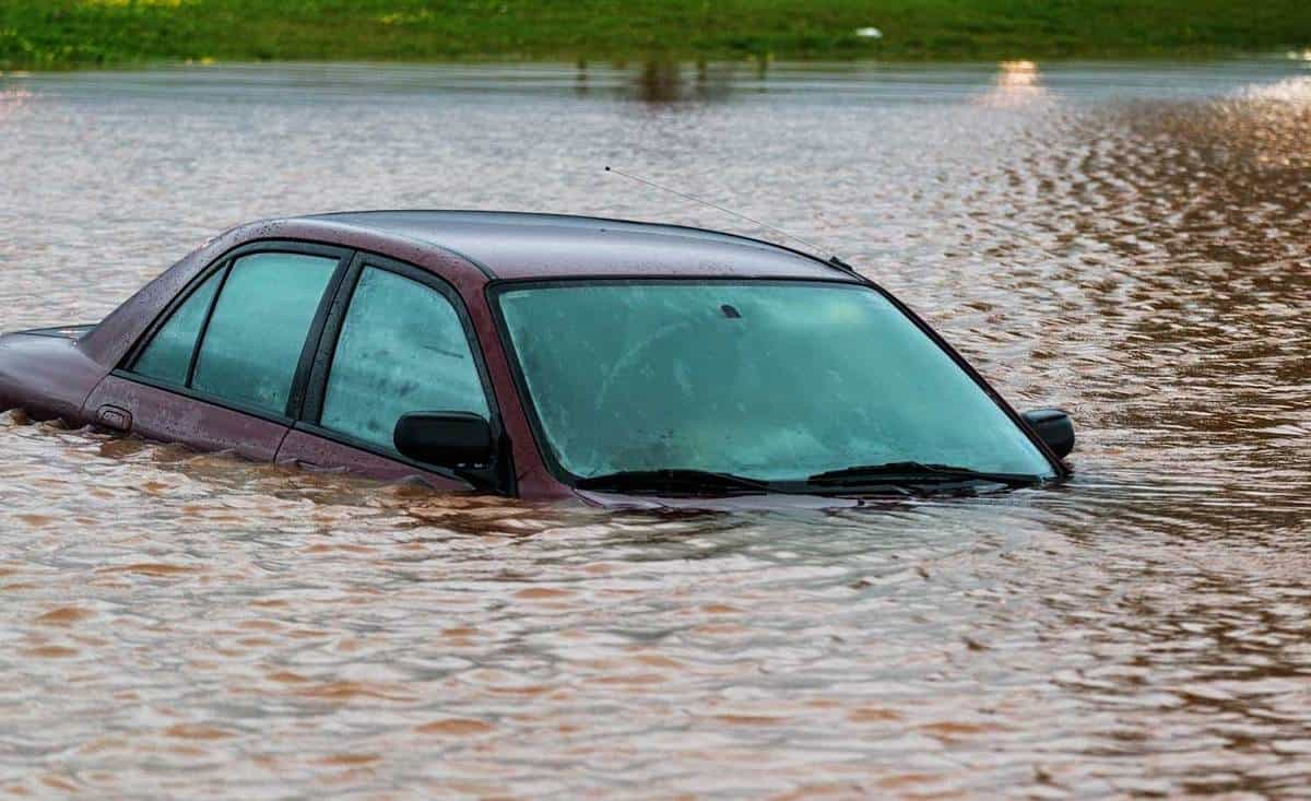 River overflows its banks and flooder a red car